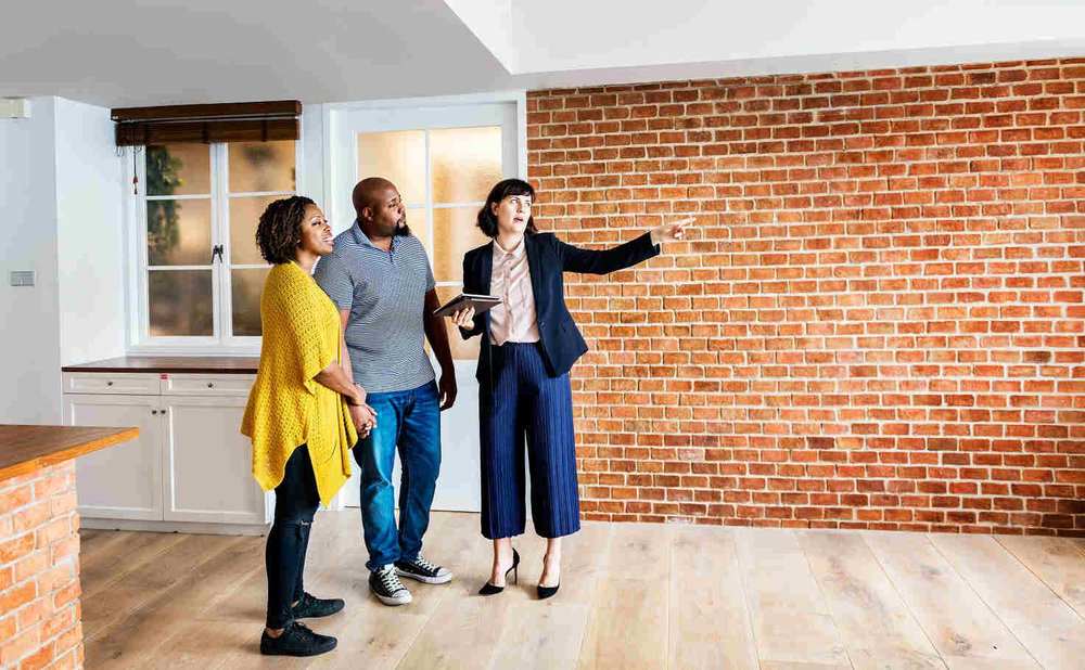 black-couple-with-realtor-in-new-house.jpg