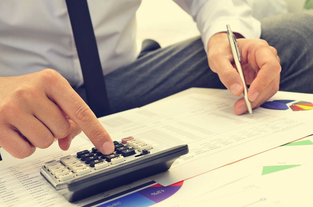 business man using calculator and writing notes
