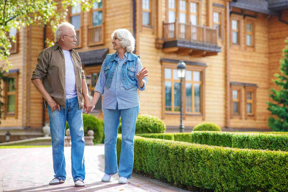 elderly couple holding hands and walking in front of home