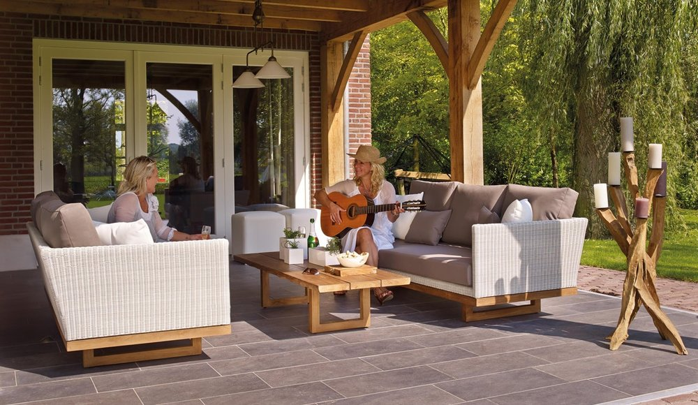 lady entertaining a woman with guitar in patio