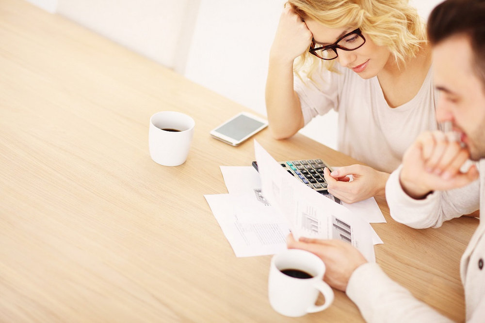 couple looking at document and making calculations on a table with coffee