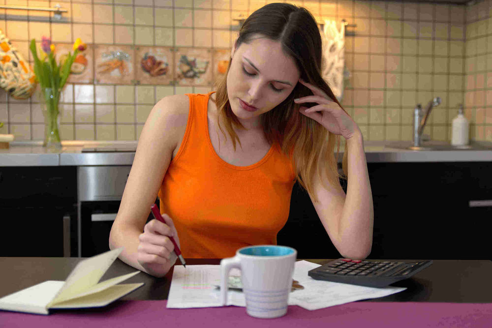 young white woman looking through documents with calculator in her kitchen