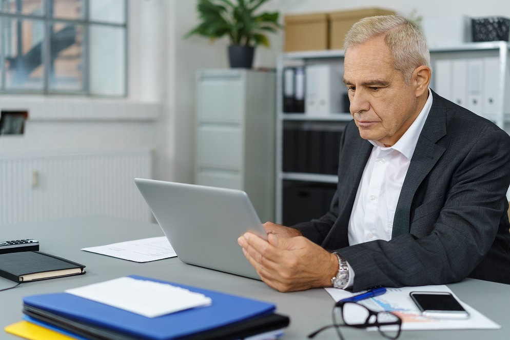 mature businessman looking at laptop in office