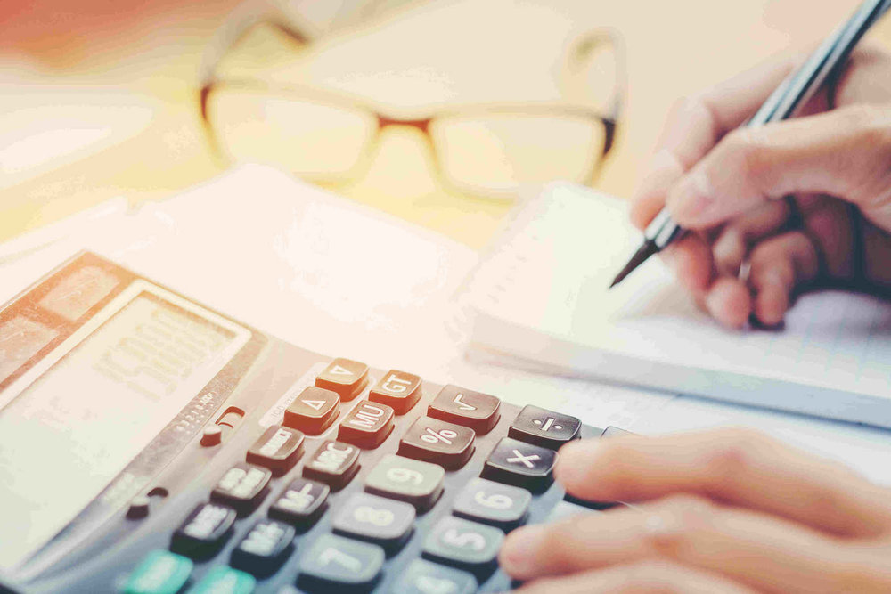hand using calculator and writing