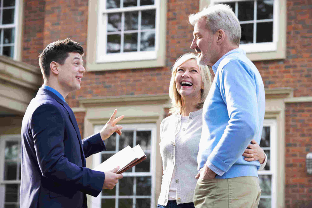 real estate agent holding documents and talking to elderly couple in front of house