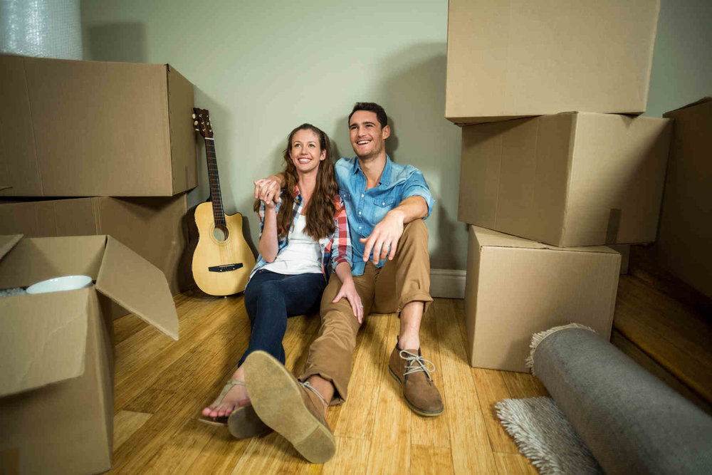 young couple seated smiling surrounded my moving boxes and guitar.jpg
