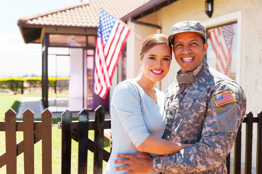 soldier and wife in front of house with american flag