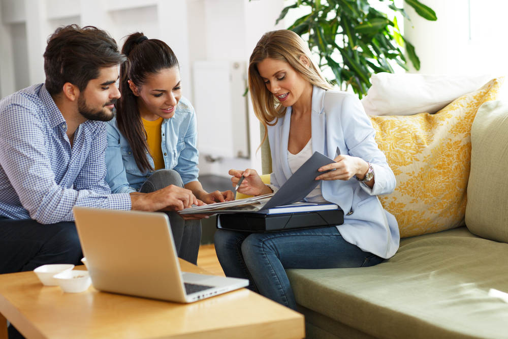 real estate agent perusing portfolio with young couple