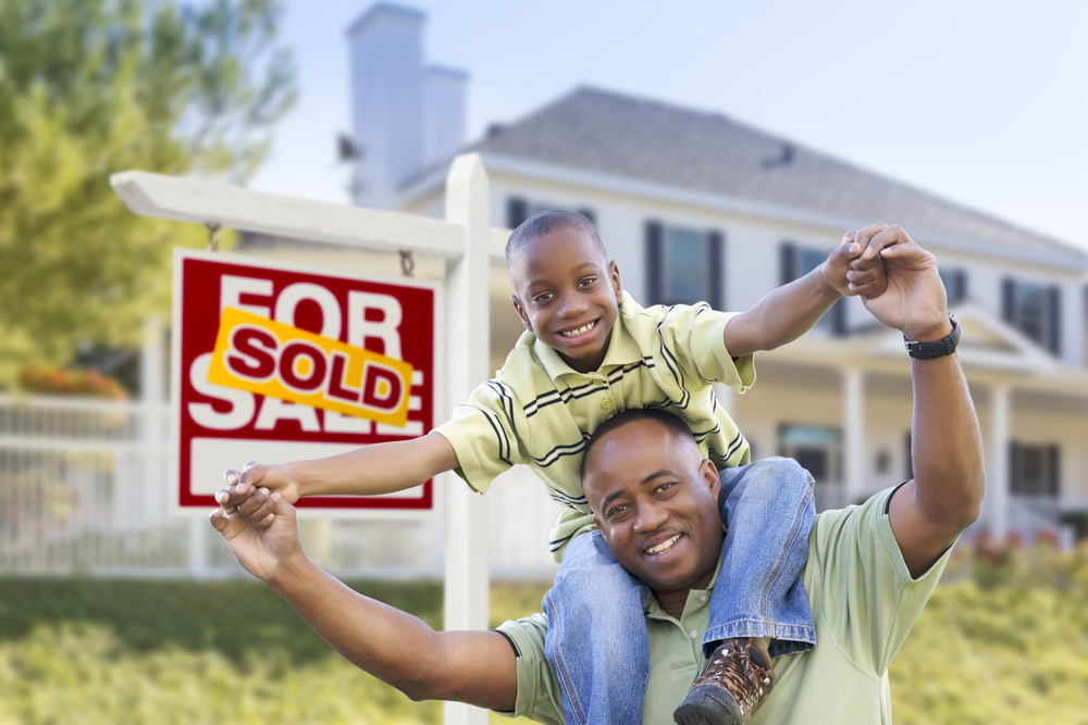 african american son on father's shoulders in front of sold house