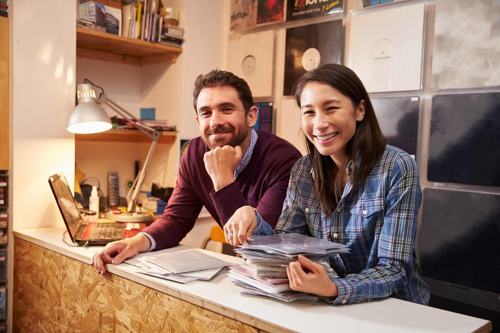 couple smiling over stacks of documents on counter