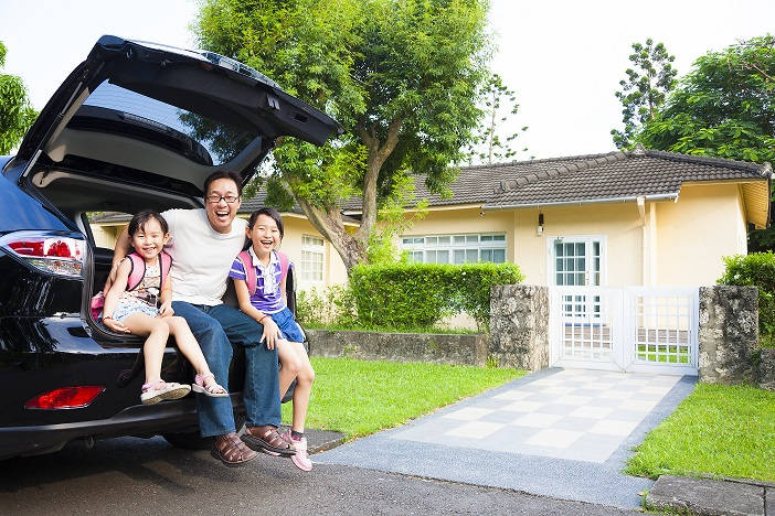 family seated in car boot smiling in front of house