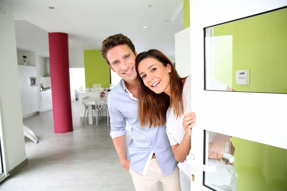 young couple open frontdoor from inside home