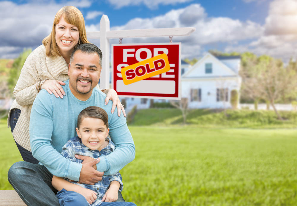 family posing infront of sold house.jpg
