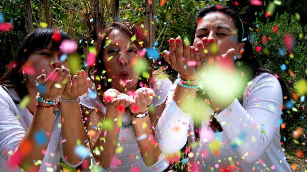 three women blowing confetti.jpg