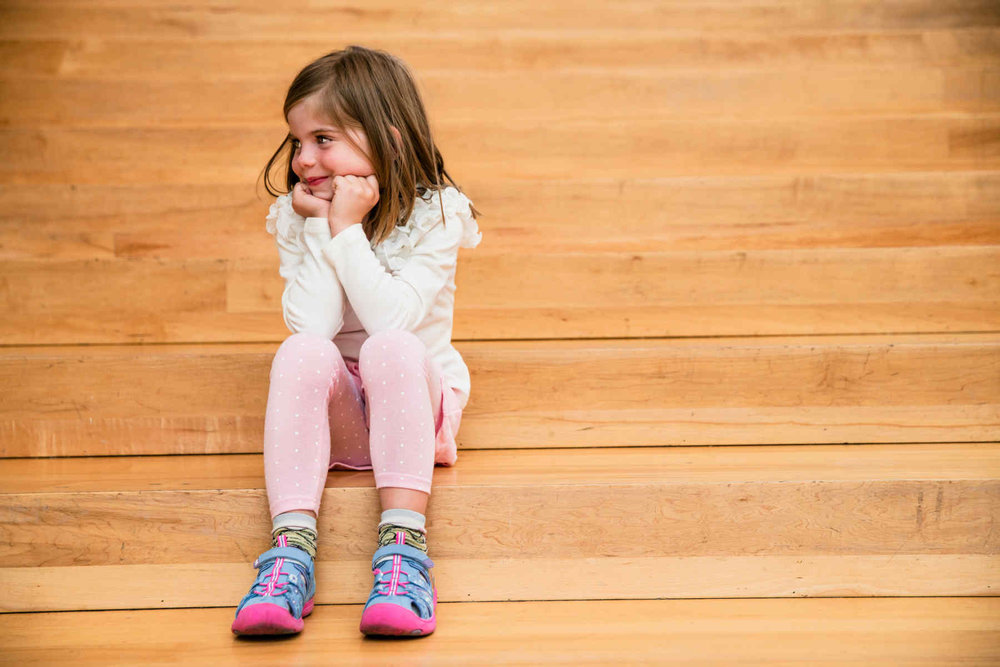 little girl seated on wooden stairs.jpg