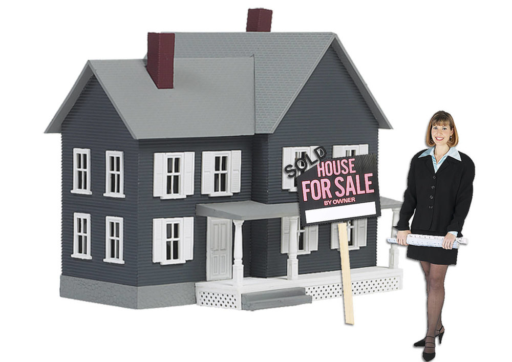female real estate agent standing next to house for sale.jpg