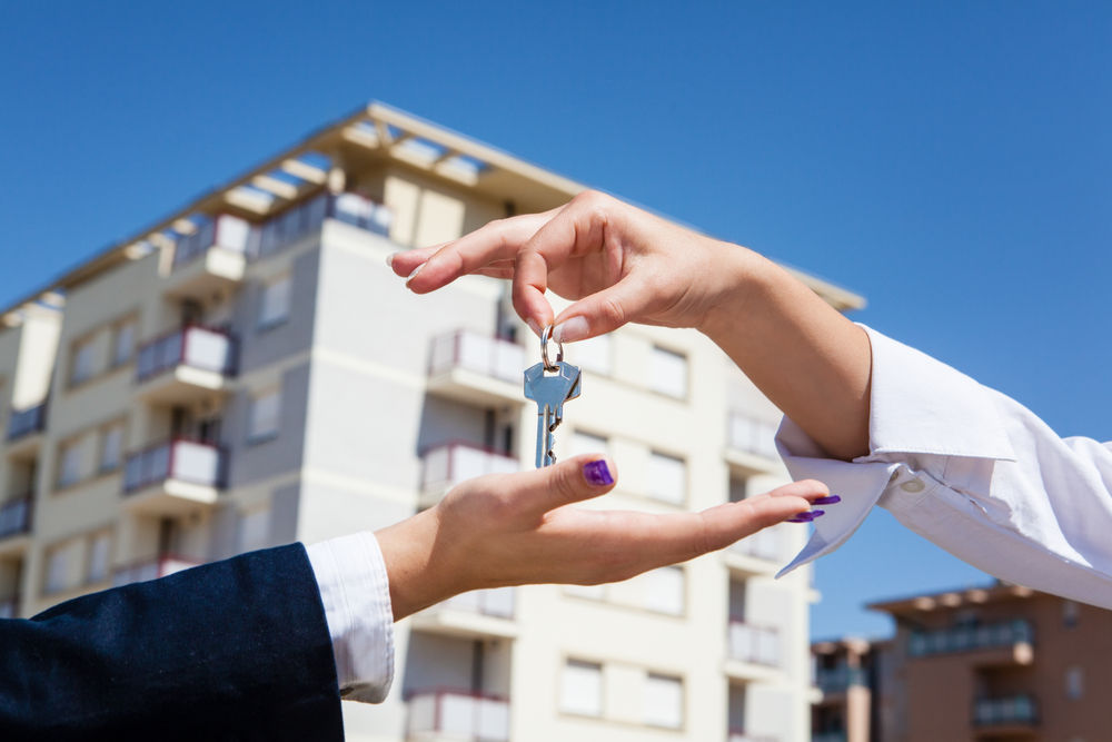male hand dropping house keys into female hand with apartments in background.jpg