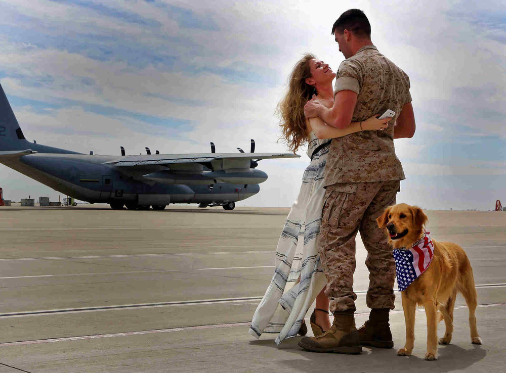 army man and wife on airstrip with dog and a plane in background.jpg