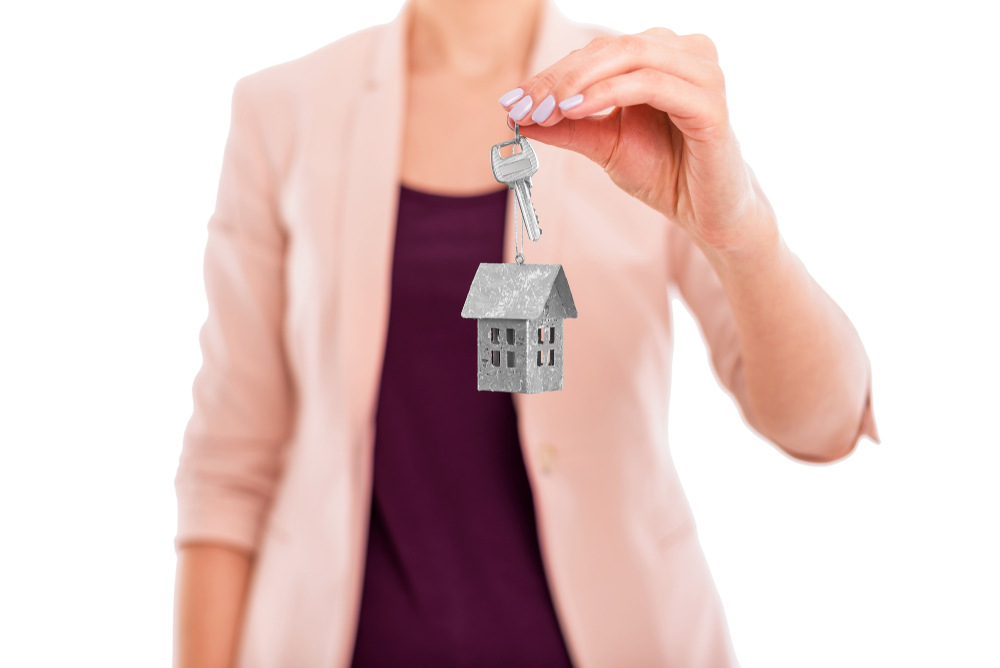lady handing over house keys with keychain.jpg