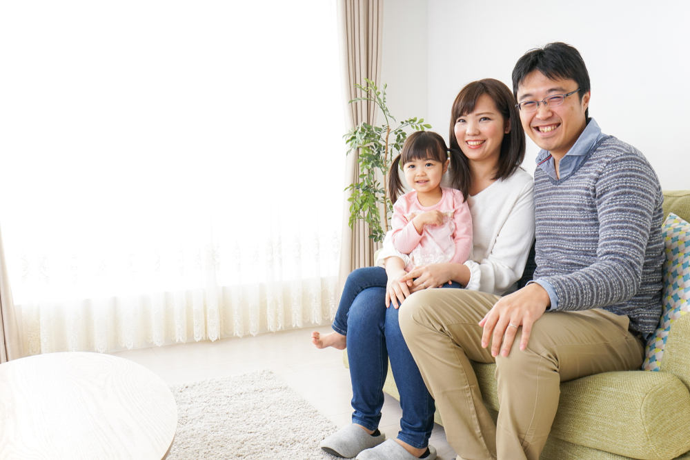 asian family seated on sofa smiling.jpg