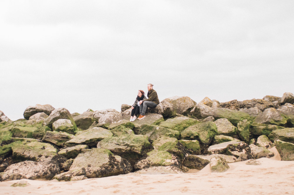 Couple sitting on rocks, New Brighton beach, wirral