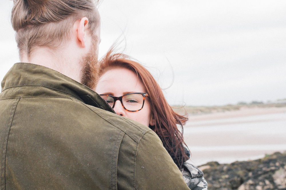 Loving gaze, Couple sitting on rocks, New Brighton beach, wirral