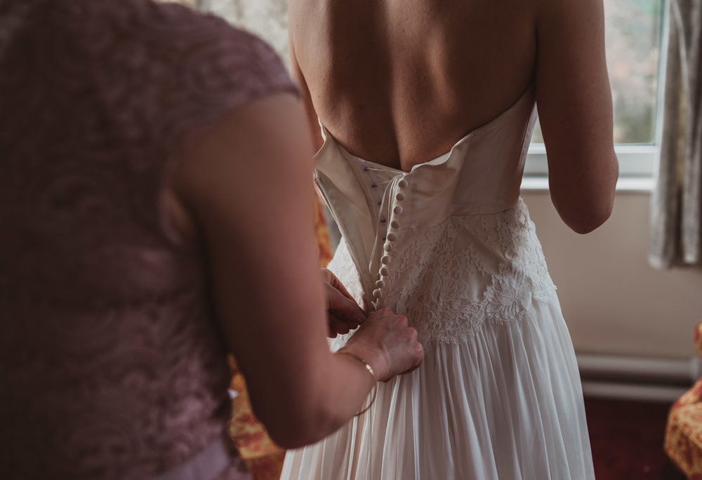 Lake District wedding - putting dress on