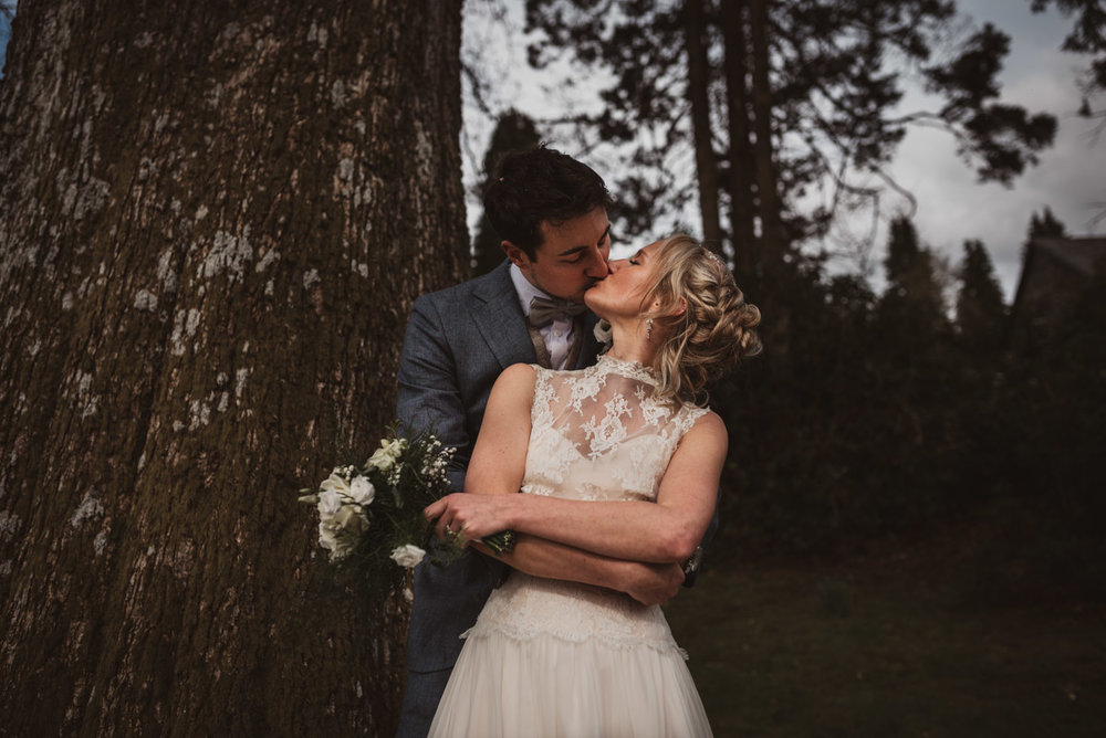 bride and groom hugging in front of tree