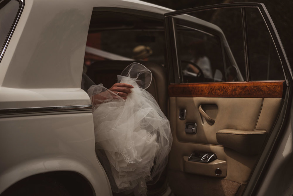 bride in car arriving for wedding