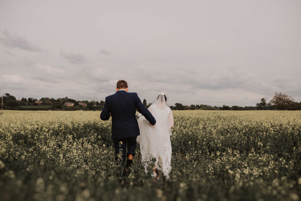 bride and groom walking on field