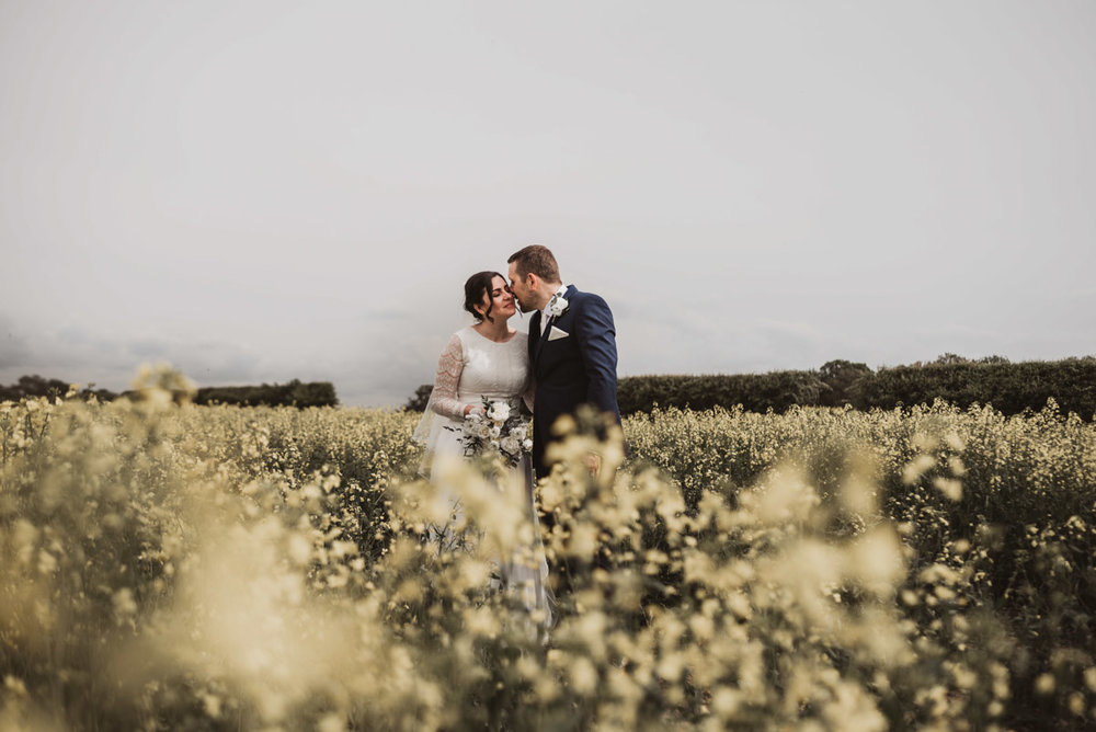 bride and groom natural in field kissing