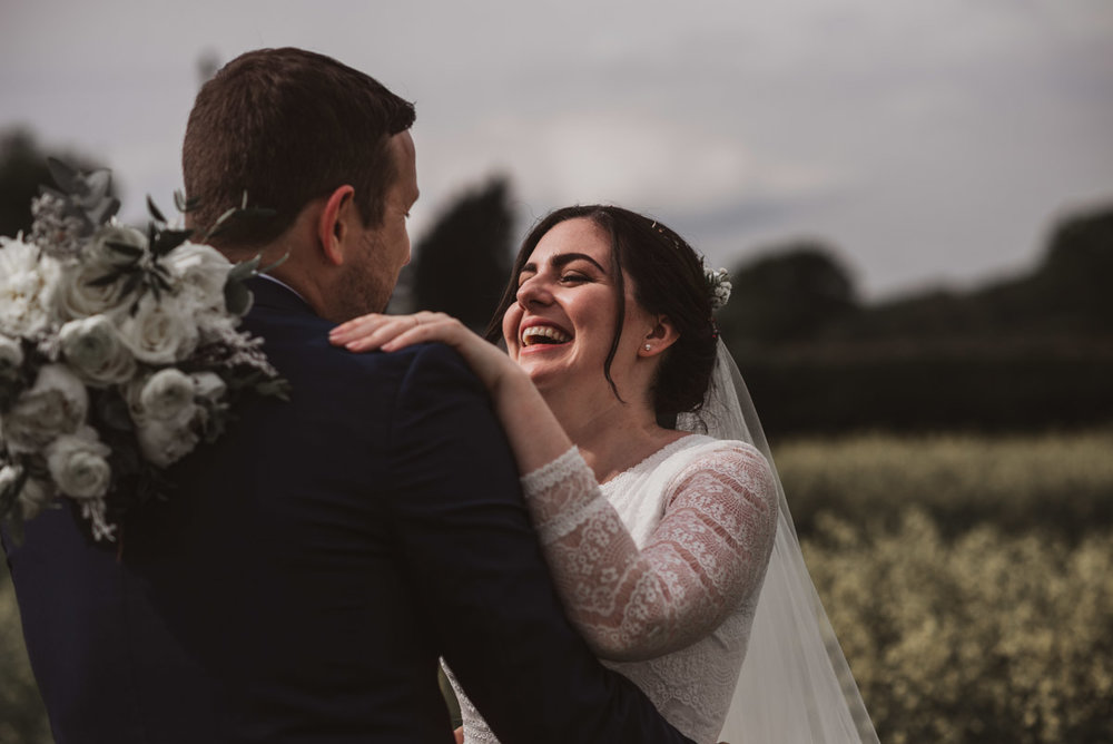 bride and groom natural laughing in field