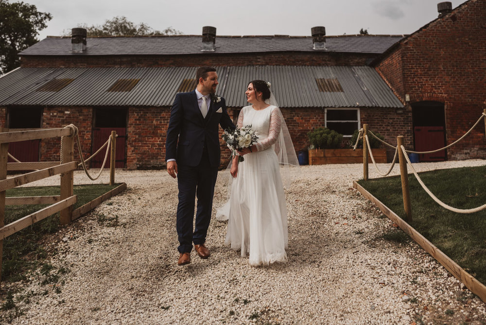 bride and groom walking past barn