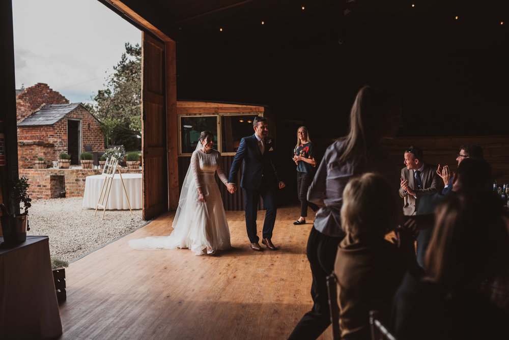 bride and groom walking in barn
