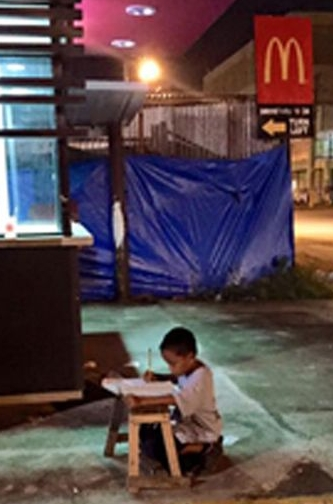Boy-studying-outside-a-McDonalds-in-Manila.jpg