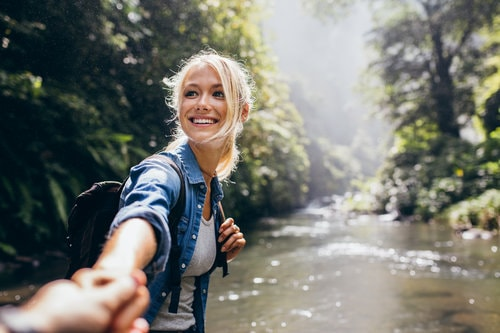 Blond woman smiling hiking by river happy not anxious