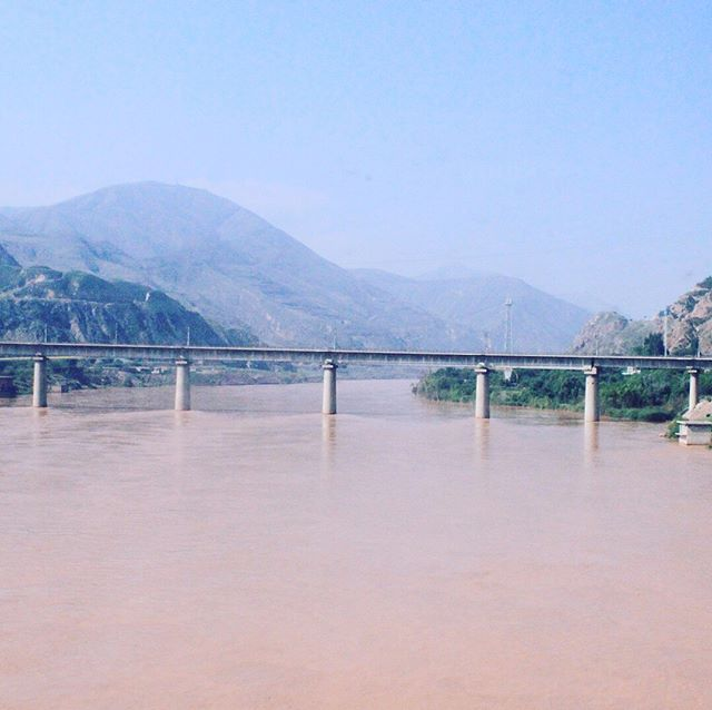 Day 55. The Yellow River. One of its many tributaries blindsiding us after 15 of 18 hours carving a smooth line of rail from Urumqi to Lanzhou, Gansu Province. The number of tunnels and bridges crossed showcases the geo-engineering capabilities China aims to export to other geographically-complex regions in Asia through OBOR. It's not often you can cross the concept being exported but Gansu gives a real sense of the BRI and its structural manual, thinking and experience to date. I still can't shirk this murky brown wide drowning the lens with green on either cornea, like the Syr and Amu-Daryas of Bishkek and Almaty a week past, the reminder comes side-window, unfurling and folding downstream, that the BRI is as much a riverine as an oceanic concept.  @jeep  @csis @uniofstandrews @magellancapital @fca_group  #beltandroad #gansu #lanzhou #yellowriver