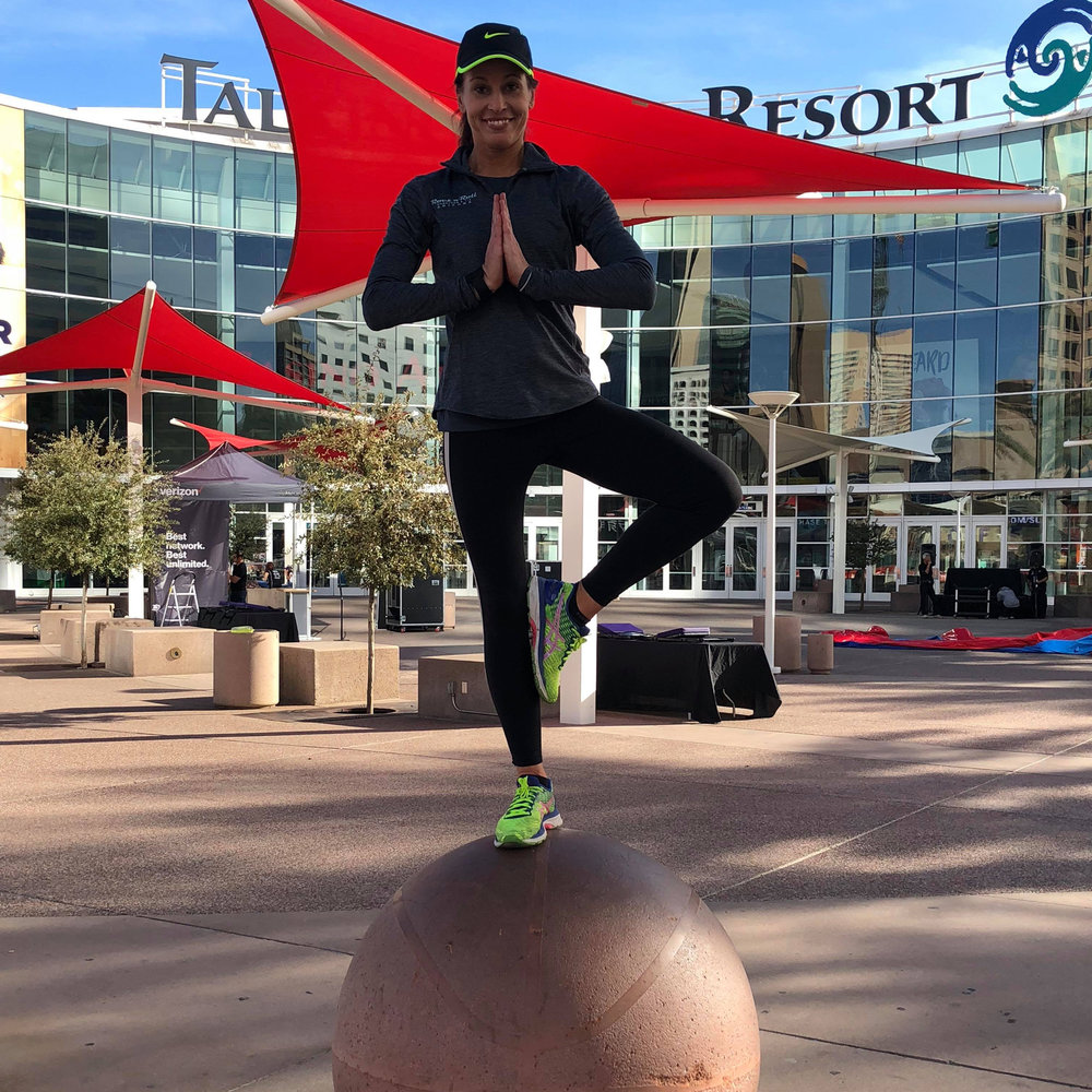 "February 2018 — DeAnn McClure   DeAnn is an avid runner who has completed several half and full marathons. She's pictured here after running the Rock 'n' Roll 1/2 Marathon in Phoenix this past January. We asked DeAnn to share a little about why she started doing yoga — ""While researching how to recover faster from running and lower risk of injury during long training days, practicing yoga kept coming up. That's when I started going to Rebecca's classes. I was nervous at first but she immediately made me feel comfortable and I knew I was in a very non-judgemental environment. I quickly became sold on the practice of yoga. I could eventually run long runs and feel energized and recovered almost immediately. I have become stronger and more centered all due to yoga. My running has improved both in my form and control. I am more flexible and can recover in a healthy way from those long distances. I know that yoga has and will continue to help me become toned and more in tune with my muscles. I love it and am so thankful to have found her class!"""