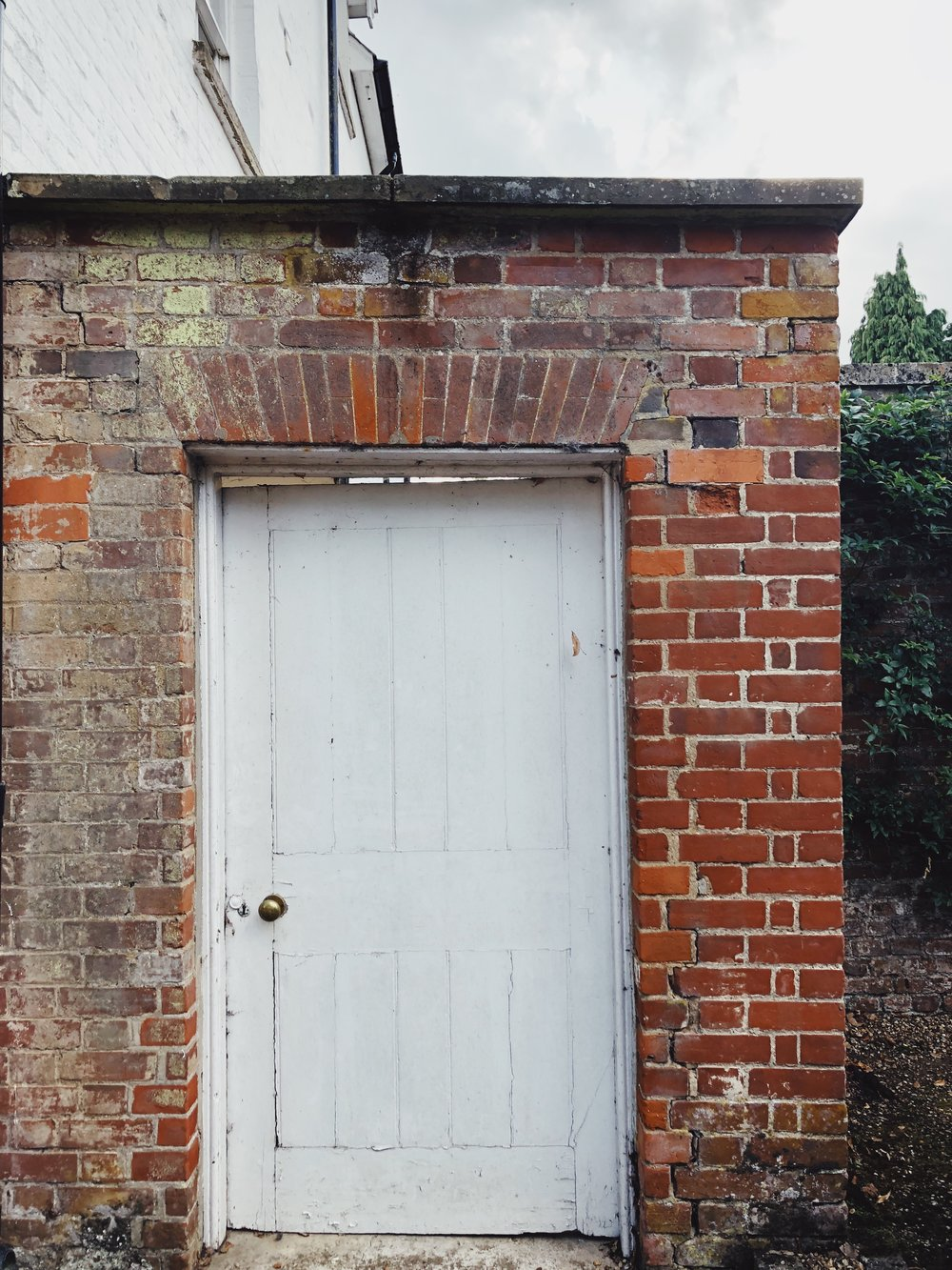 white door in a brick wall.