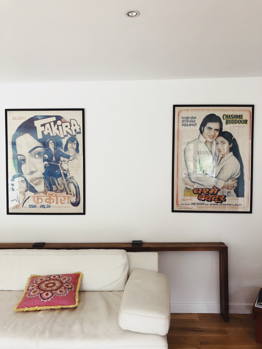 old bollywood posters on the wall of a living room