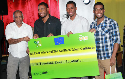 From left, Guyanese Agriculture Minister Dr Leslie Ramsammy presents the first-place prize cheque for 5,000 euros to Matthew Mc Naughton and Jamaican team Node420, at the award ceremony for the Agrihack Caribbean Talent competition in Paramaribo, Suriname, on October 9. Photo courtesy: The Technical Centre for Agricultural and Rural Cooperation ACP-EU (CTA).