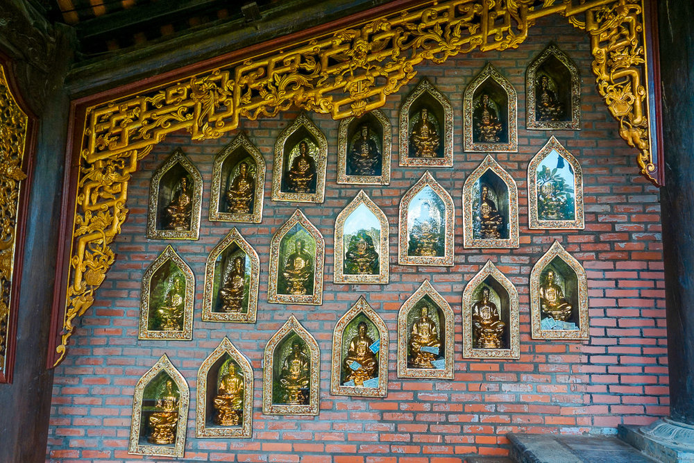 The hallways of the Bai Dinh temple complex had hundreds of small buddha statues behind glass. Many of the locals had left money by the statues as an offering.