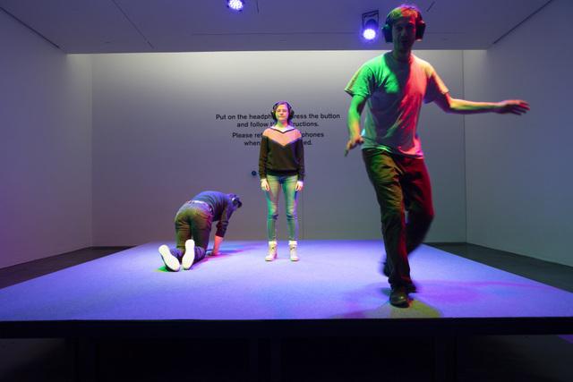 Christian Falsnaes  Stage , 2017. Stage, carpet, stage lights, audio on headphones, visitors. Ph: Finnish National Gallery / Pirje Mykkänen
