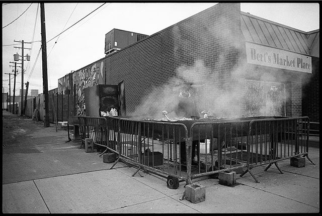 """Bert's Market Place"" • Can you find the smoke master in there somewhere?  Eastern Market on Saturday morning, the amazing smells from the west side of Russell Street moving through the market are almost enough to make this semi-vegetarian question my reasons for forgoing ribs. • Check out the vignette from the 28mm nikon. I love it. • Nikon F2 Nikkor 28mm f/3.5 Ilford hp5+ • #nikonf2 #ilfordhp5 #ilfordfilm #film #blackandwhite #filmisnotdead #filmisalive #filmphotographic #photofilmy #filmphotography #heyfsc #filmcommunity #ishootfilm #believeinfilm #buyfilmnotmegapixels #35mm #35mmfilm #analog #analogphotography #filmcommunity #justgoshoot #staybrokeshootfilm #shotonfilm"