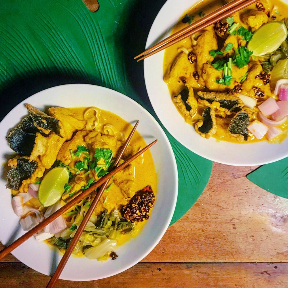 CHIANG MAI KHAO SOI - Rich, creamy, and packed with flavour, this aromatic dish is an icon of the Northern province of Chiang Mai. Slurpishly moreish noodles, decadent broth, fried tofu puffs, and a medley of colourful toppings, Khao Soi is one of our most requested dishes - and when you taste it, you'll know why!