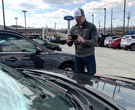 Akron Auto Auction Condition Report Writer, Kyle Feemster, takes photos of Virtual Lane vehicle at a Ford Dealership