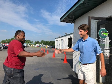 Kevin Stallings (right: Assistant General Manager at Greenville Auto Auction) greets Derrick Speight (Miller Auto Brokers) before the auction on Thursday.
