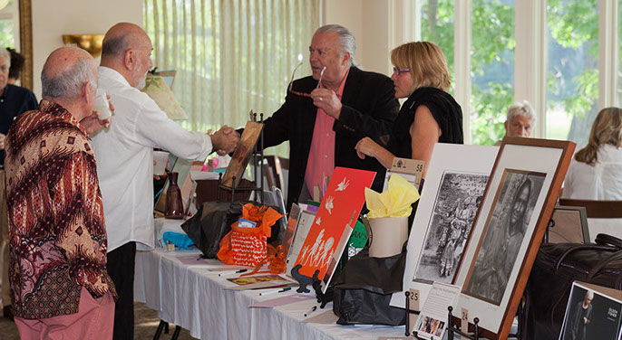 Attendees glance at the many ítems in the silent auction. Click here for more images of the great event.