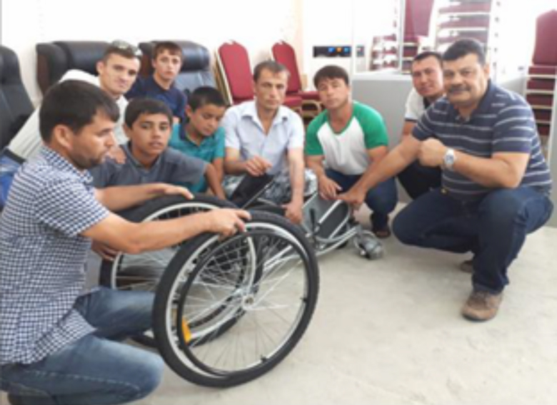 WHO Trained Wheelchair Technician, Santiago Castellón working with participants to assemble the wheelchairs