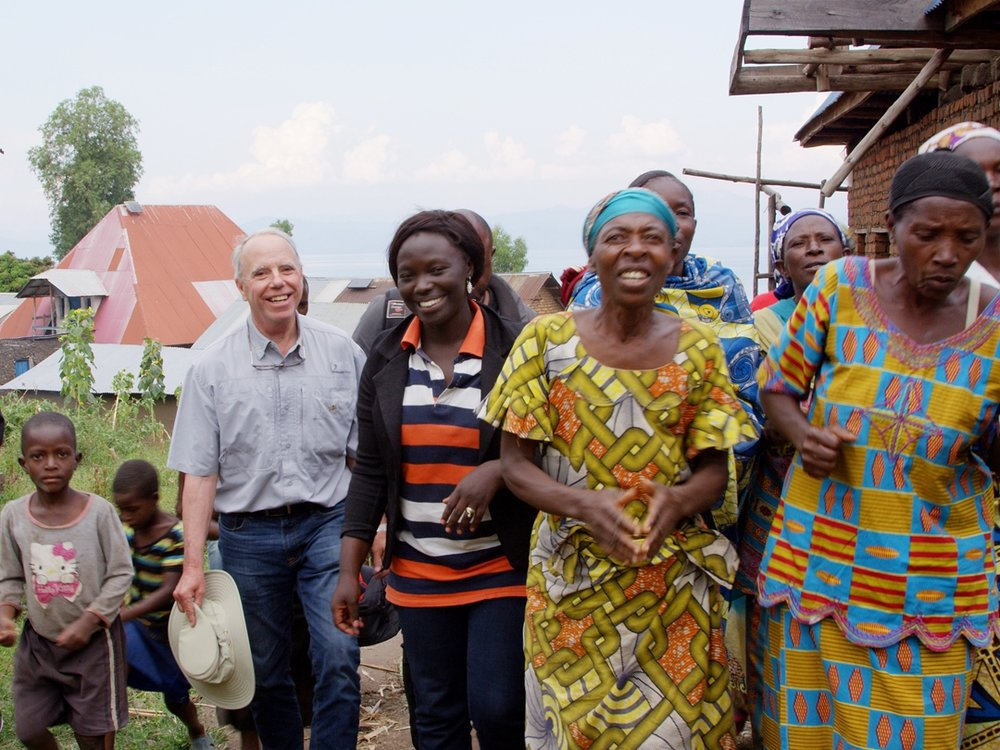 At Rebuild Women's Hope coffee coorperative, Marceline Budza, the Coop AG (center), provides Michael Lundquist (left) and the delegation with a tour of their washing station after a warm welcome from coop members with singing and well wishes.